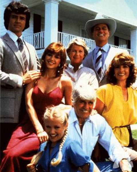 """Dallas Türkiye'de çok yuvalar yıktığı iddia edilen efsane dizi. Dallas başladı mı sokaklar boşalır, çocuklar erkenden yatırılırdı. Eğer kalabalık izleniyorsa bazı sahnelerinde kadınlar kendilerini mutfağa su almaya gitmeye mecbur hissederdi. Kötü adam Jr. Ewing'i kimin vurduğu üzerine bahisler açılmıştı. Bayan Ellie """"çok hanım"""" olduğu için çok sevilmişti. Dallas'ı çok sevmiştik çok."""