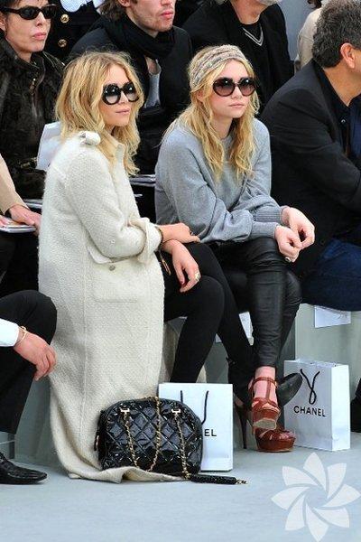"""""""Bizim Ev"""" dizisiyle çocuk yaşta televizyon dünyasına giriş yapan ve sonrasında çevirdikleri tıpatıp ikizler film serisiyle Hollywood'un sarışın ikizleri olan Mary-Kate ve Ashley Olsen kardeşler moda dünyası için de oldukça özeller. Lüksü minimal tasarımlarla buluşturan markaları """"The Row"""" her geçen sezon yükselişine devam ederken, ikizler tasarımlarıyla olduğu kadar kendi stilleriyle de birçok kişiye ilham veriyor."""