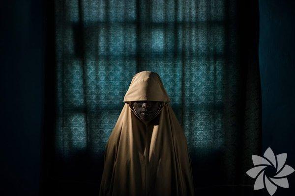 İnsanlar - Öyküler kategorisi, Birincilik Ödülü Aisha, 14 yaşında ve bu fotoğraf Nijerya'nınBorno Eyaleti'nde çekildi.Aisha, Boko Haram tarafından kaçırıldı ve intihar bombacısı görevi verildi. Vücudunu patlayıcılarla doldurduktan sonra, kendini ve başkalarını havaya uçurmak yerine yardım bulmayı başardı.